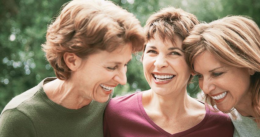 Three women with dental implants share a laugh